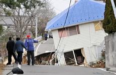 Des habitants constatent les dégâts causés à une route et une maison de la ville de Sukagawa dans la préfecture de Fukushima